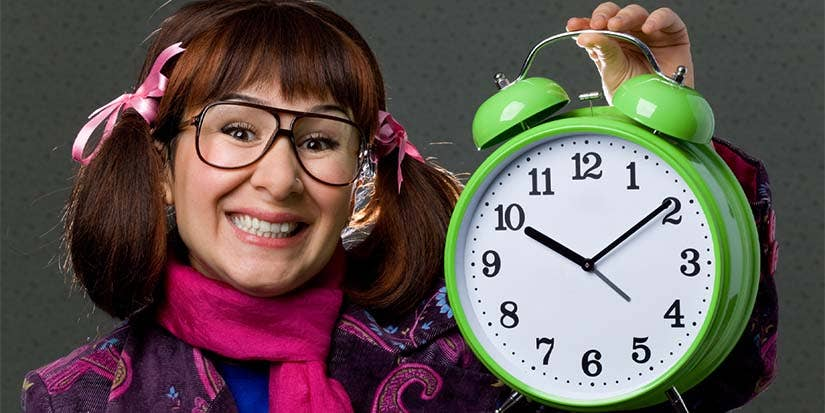 Nerdy looking girl holds up a large, green alarm clock.