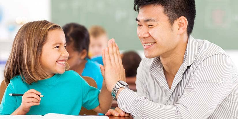 A teacher and his student high-five after a successful learning experience.