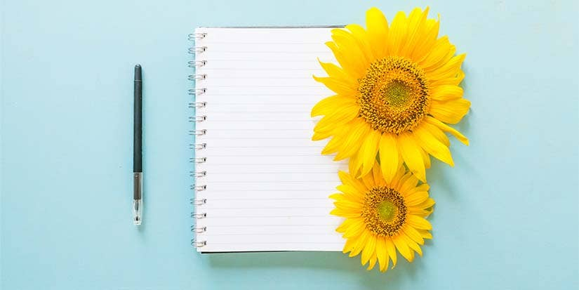 Two yellow sunflowers sit beside an open notebook atop a light blue table top.