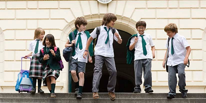 School children run down the steps of an educational institution on their way toward increased intellectual fortitude.