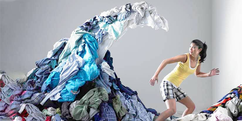 A woman runs from a tidal wave of clothing.
