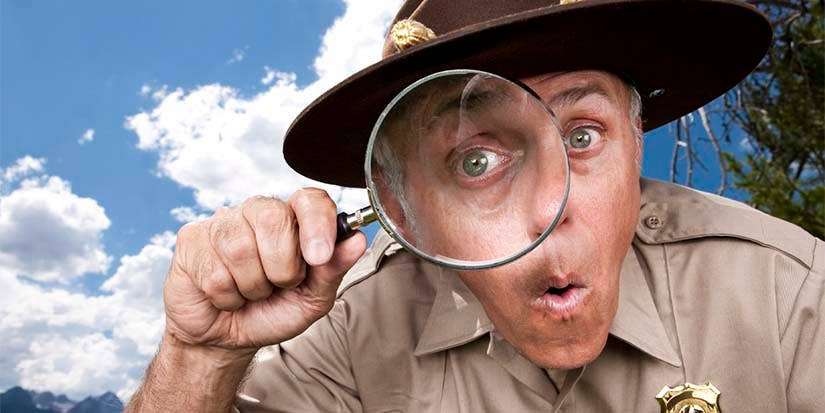 A police office peers through a magnifying glass with an animated facial expression.