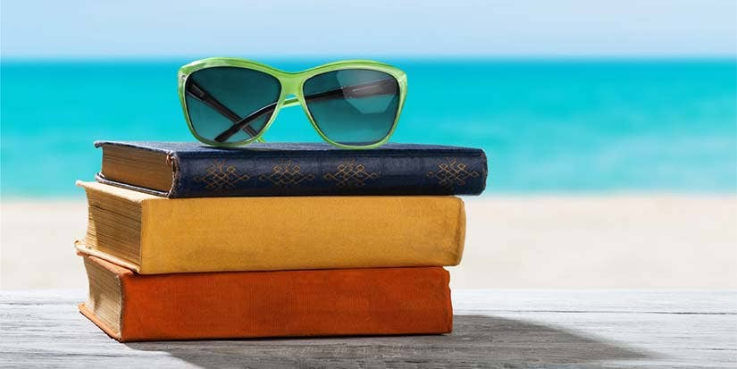 Sunglasses atop a stack of books on a sunny beach.