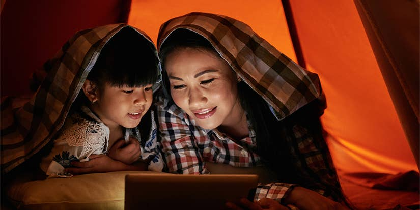 A mother and daughter watch a tablet while in a tent.