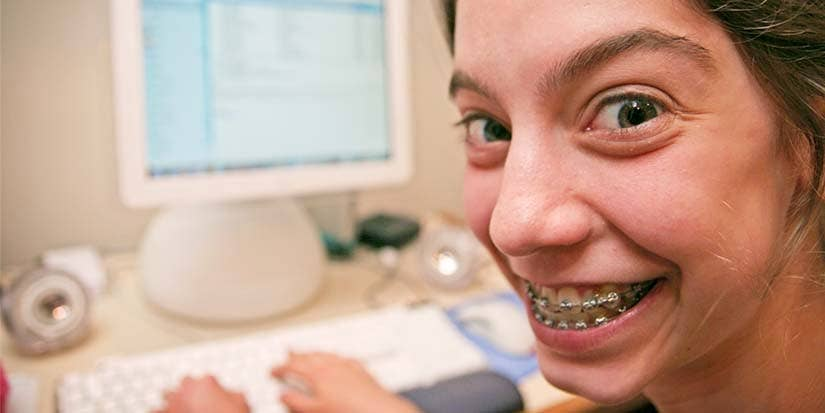 A teenage girls looks excitedly into the camera as she types at a computer.