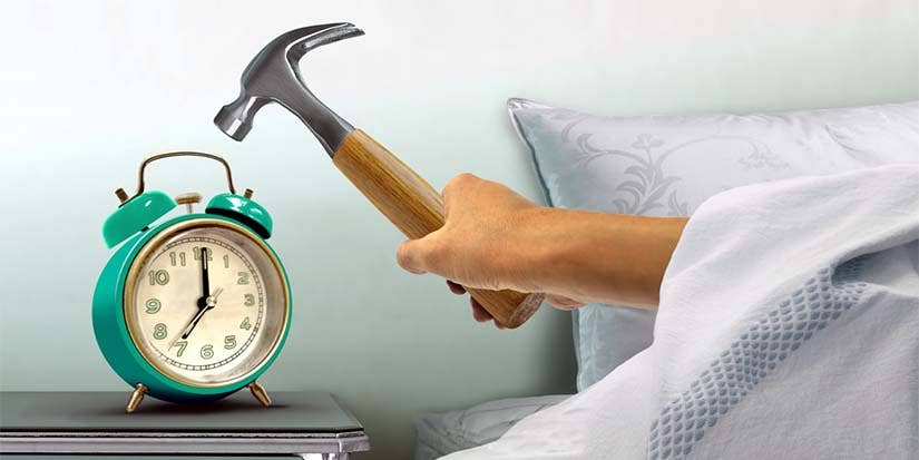 A hand emerging from the covers of a bed while holding a hammer prepares to smash an alarm clock.