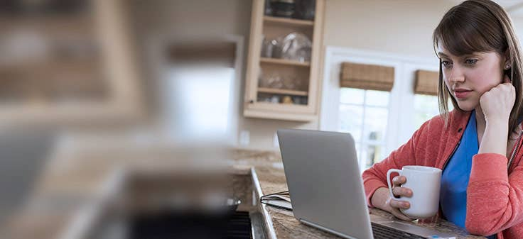 Woman looking at laptop in kitchen